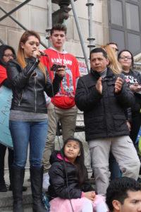 Valeria Ruiz explica a la multitud reunida sus razones para demandar Daca y Dapa, al costado su padre aplaude emocionado.