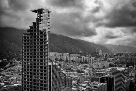 """La llamada """"torre de David"""" representa el fracaso de las políticas del gobierno en materia de barrios. Durante muchos años el edificio fue la barriada más grande del mundo de estructura vertical. Fue construido para ser un icono de la modernización de Caracas iba a ser el octavo edificio más alto de Latinoamérica, sin embargo se convirtió en el mayor símbolo de la terrible crisis social en que se encuentra entrampada la sociedad venezolana."""