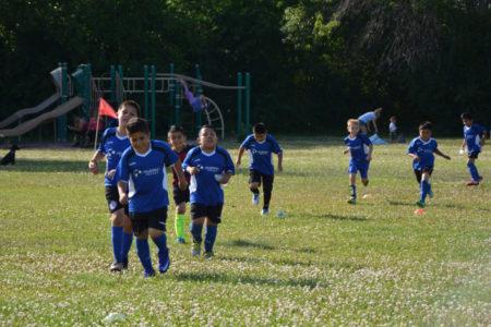 Los niños de Millennium Soccer Club hacen calentamiento antes de jugar.